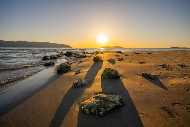 岩の多い海岸の夕日の風景の上の赤い空