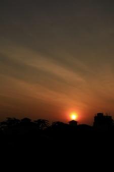 아침에 태양과 건물이 있는 붉은 하늘. 도시에서 일출입니다. 낮은 키. 자연 배경 개념입니다.