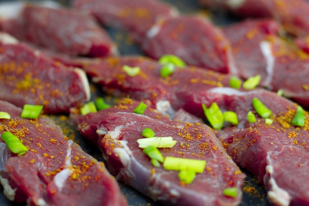 Red slices of fresh veal with spices of paprika and onion, sliced into raw thin beef steaks