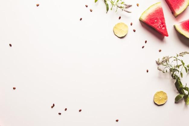 ミントの葉と白い背景の上のライムスライスと熟したスイカの赤いスライス。上面図、フラットレイ、コピースペース