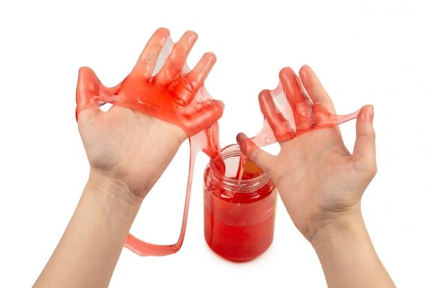 Игрушка из красной слизи в руках женщины