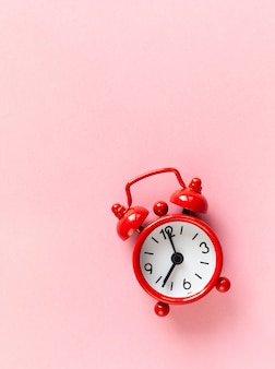 Red small alarm clock on pastel pink background with copyspace.
