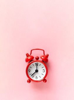 Red small alarm clock on pastel pink background