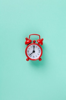 Red small alarm clock on pastel turquoise background with copyspace.