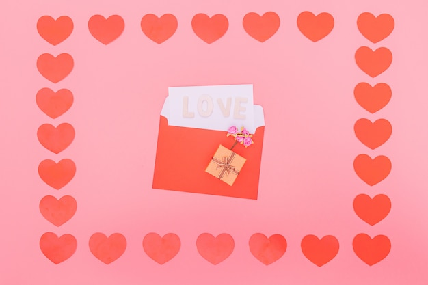 Red small hearts around a red envelope on pink