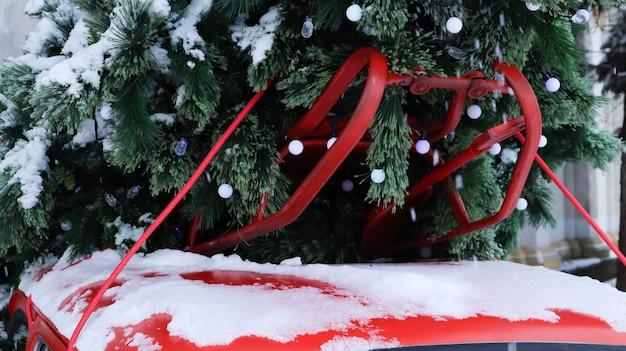 지붕에 묶인 크리스마스 트리 전나무와 빨간 작은 복고풍 자동차. 크리스마스 휴일 장식, 가족 축하 상징을 위한 신선하게 자른 천연 가문비나무.