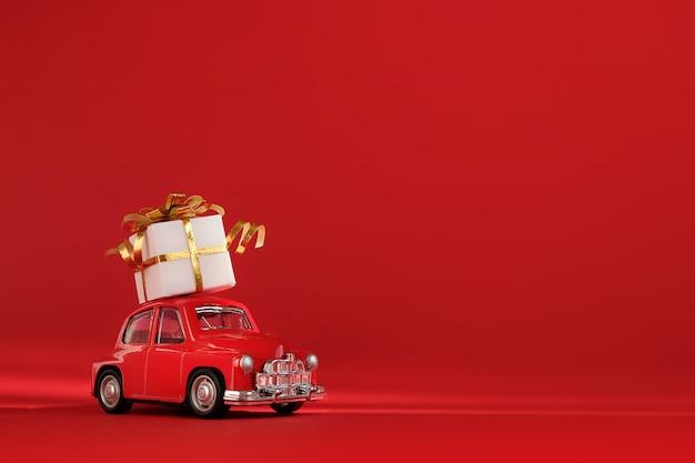 Красный маленький ретро игрушечный автомобиль с подарком на крыше.
