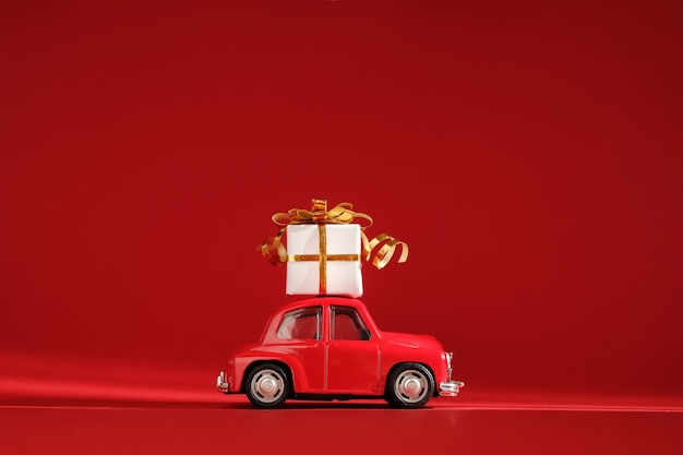 Red small retro toy car with gift on the roof.
