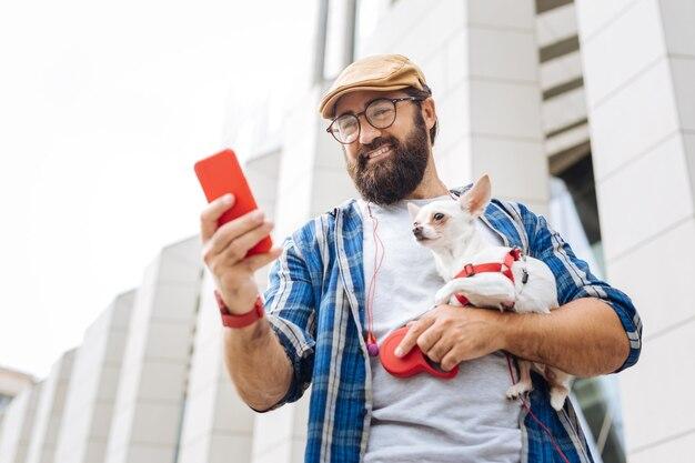 레드 스마트 시계. 강아지와 함께 도시를 걷는 동안 빨간색 스마트 시계 입력 메시지를 입고 현대 프리랜서