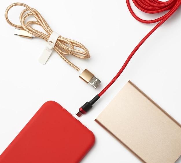 Красный смартфон и кабель в текстильной оплетке на белом пространстве