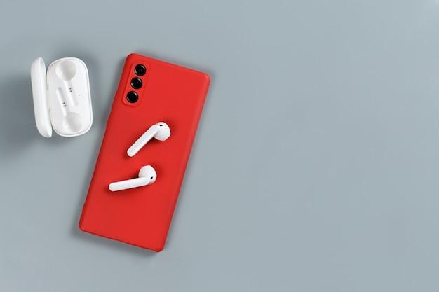 灰色の背景の上面図に赤いスマートフォンとワイヤレスイヤホン