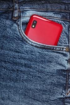 フロントジーンズのポケットに赤いスマートフォン