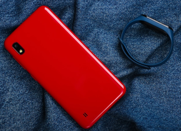 Red smartphone and smart bracelet on jeans