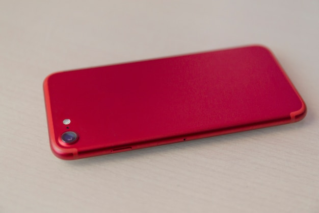 Red smartphone over wood