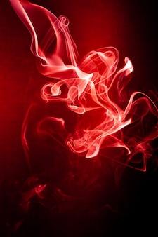 黒の背景に赤い煙の動き。