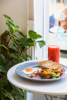 Red smoothie and breakfast on white table near the window