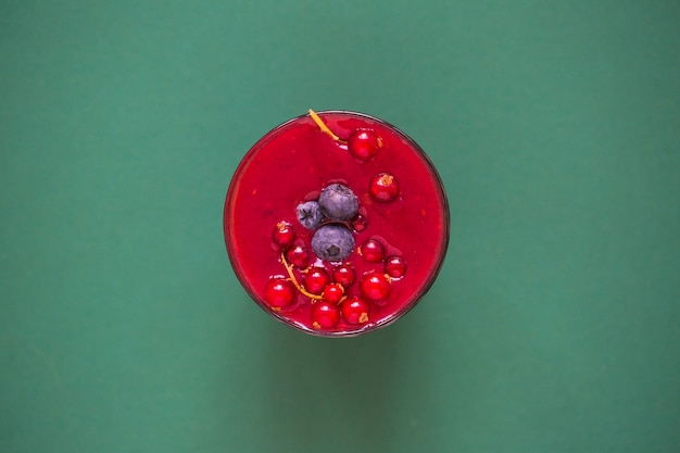 Red smoothie with berries in glass on green background