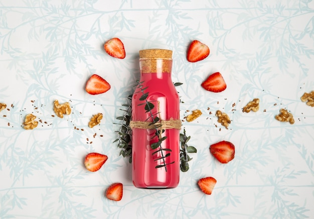 Red smoothie with nuts seeds on cute background