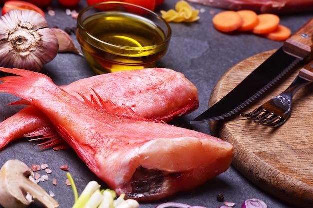 Красный окунь с маслом и чесноком рядом со столовыми приборами