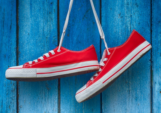 Red sneakers hanging on a wooden blue