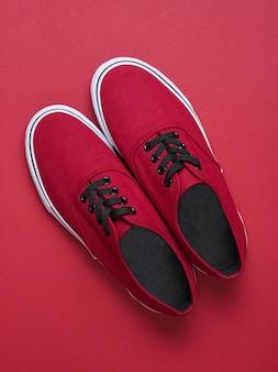 赤いテーブルに赤いスニーカー。ミニマリズム、ファッション、トップビュー