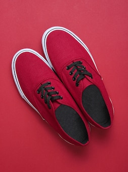 Red sneakers on a red table. minimalism, fashion, top view