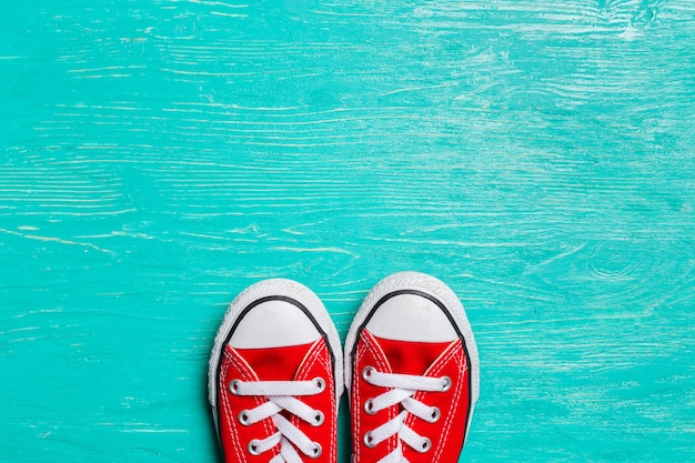Red sneakers on wooden background.