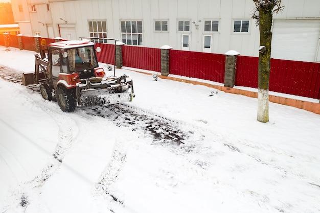 赤い除雪車トラクターが歩道の背面図をクリアします。