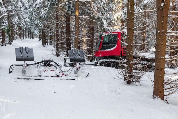 冬の雪に覆われた森の赤いスノーモービル