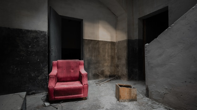 Red sofa in a dark, grey and abandoned house