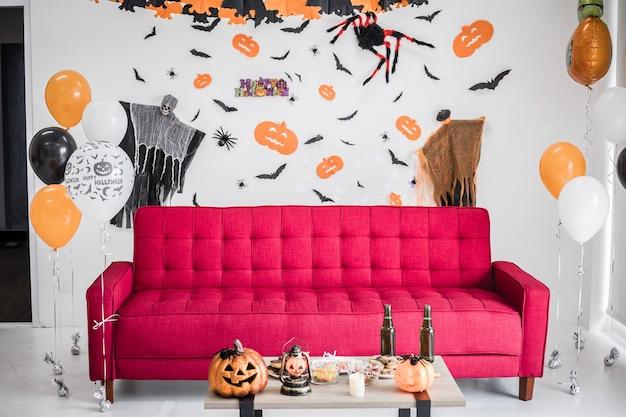 장면이 있는 방의 빨간 소파는 할로윈으로 설정되어 있습니다. 매달려 있는 장식품, 할로윈 축제의 장면들이 방의 벽에 걸려 있습니다. 할로윈 장식의 장식입니다.