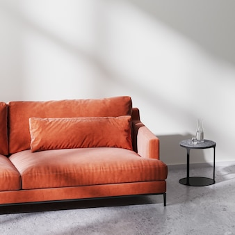 Red sofa with black coffee table in empty room with white empty wall with sun rays, raw concrete floor, scandinavian minimalistic style, 3d rendering