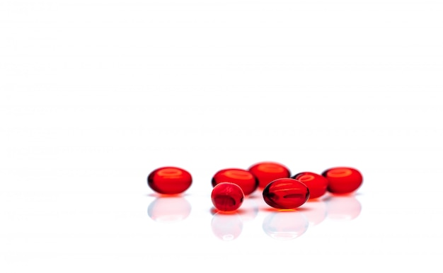 Red soft gel capsule pills isolated. pile of red soft gelatin capsule. vitamins and dietary supplements concept. pharmaceutical industry.
