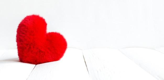 Красное мягкое сердце на белом деревянном фоне на день святого валентина с копией пространства