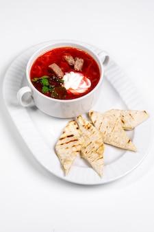 白い皿に赤いスープ。パンの前菜とボルシチ。