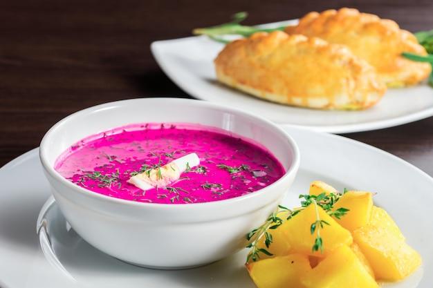 ジャガイモとパイの皿の上の赤いスープ