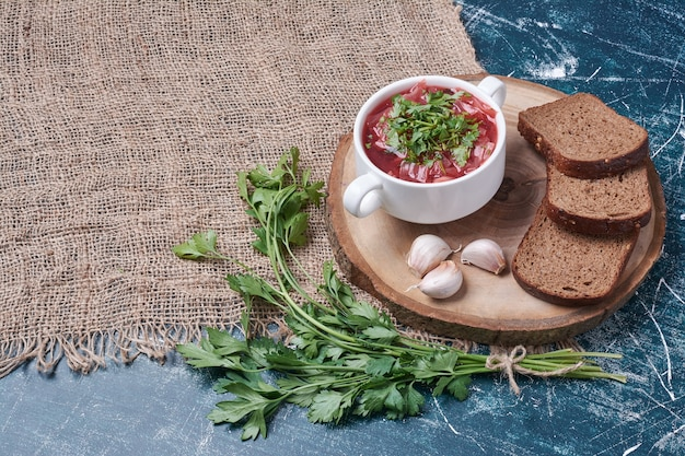 Red soup with herbs and bread slices.