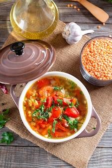 木製のテーブルにレンズ豆と野菜の赤いスープ。健康食品、健康食品。上面図