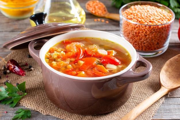 木製のテーブルにレンズ豆と野菜の赤いスープ。健康食品、健康食品。