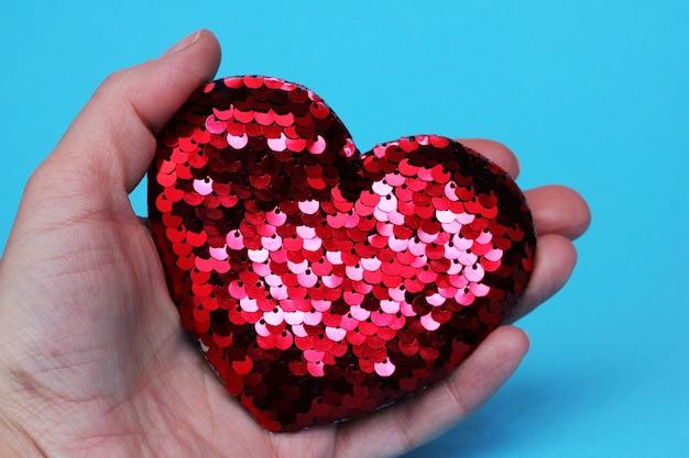 Красное сверкающее сердце с блестками в руке на синем фоне. концепция дня святого валентина. идея любви и подарков. идея предложения руки и сердца.