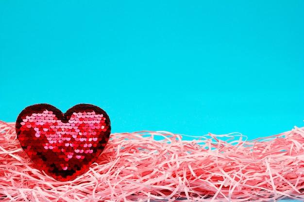 Красное сверкающее сердце с блестками на синем и розовом фоне. концепция дня святого валентина. идея любви. скопируйте пространство.