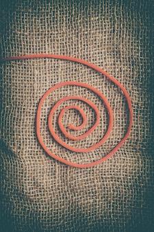 ジュートの背景に赤いらせん状の糸。本の表紙に最適な抽象的な縦長の画像。
