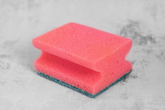 灰色の背景に皿を洗うための赤いスポンジ。クリーニングサービスのコンセプト、クリーニングアクセサリー。