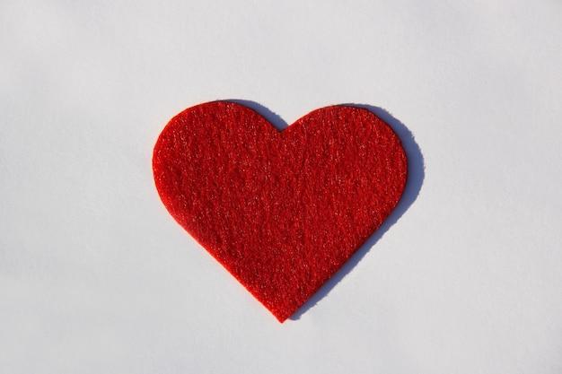白い紙の背景の上の赤い海綿状のベルベットの心愛の概念