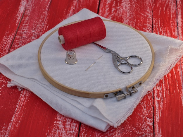 Red spool of thread and fabric in the wooden embroidery hoop