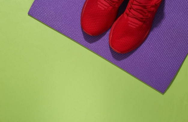 Red sport shoes and fitness mat on green background. workout concept. copy space