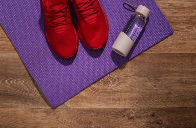 木の床に赤いスポーツシューズ、ウォーターボトル、フィットネスマット。ワークアウトの概念。