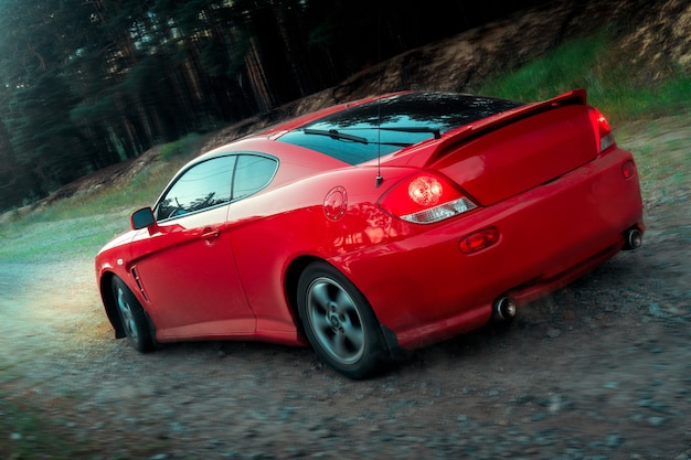 Red sports car moves over rough terrain with headlights backview