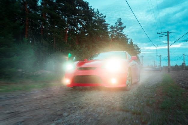 Red sports car moves over rough terrain with headlights