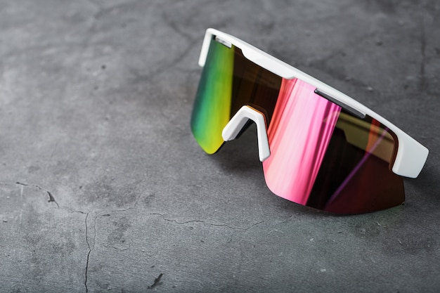 Red sports glasses with a mirror lens on a dark surface